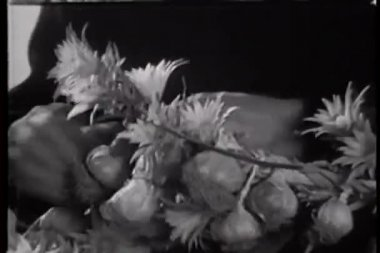 Close-up of hands interlacing flowers and garlic into wreath — Stock Video