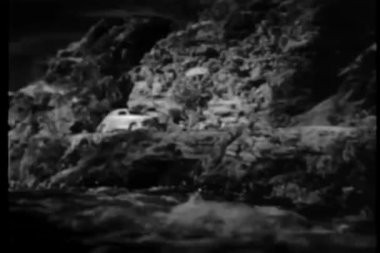 1940s car swerving off road into river — Stock Video