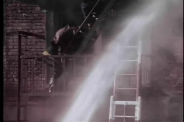Firemen rescuing victim on fire escape of burning building — Stock Video