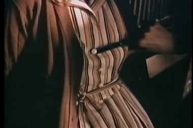 Close-up of hand with scissors cutting button on dress — Stock Video