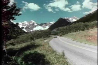 Retro bil körning på bergsväg på solig dag — Stockvideo