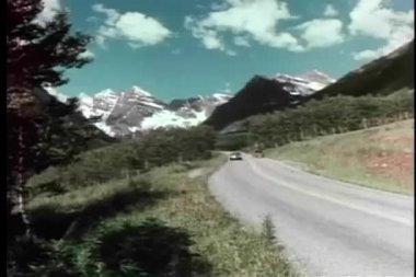 Retro car driving on mountain road on sunny day — Stockvideo