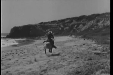 Man on galloping horse riding across the beach — Stock Video