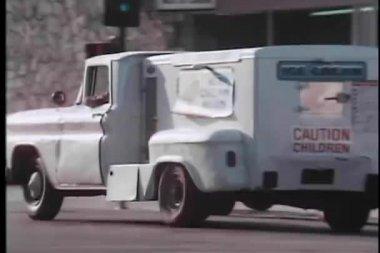 Ice cream truck driving through traffic — Stock Video