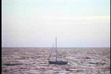 Wide shot of a sailboat drifting on an open ocean — Stock Video