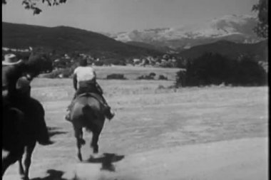 Rear view of cowboys on horses galloping through prairie land — Stock Video