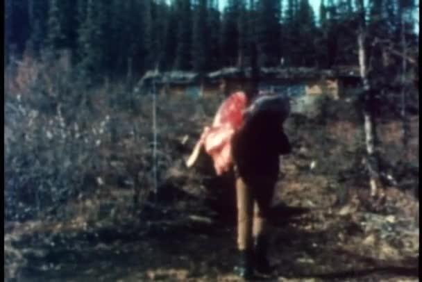 Vue arrière de l'homme transportant des carcasses à travers désert — Vidéo