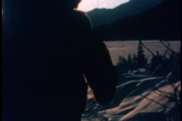 Vue arrière de l'enfant marchant sur le chemin dans la neige au coucher du soleil — Vidéo