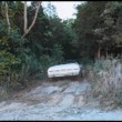 Man driving convertible down dirt road into woods — Stock Video
