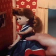 Stock Video: Close-up of girl's hand playing with doll in dollhouse
