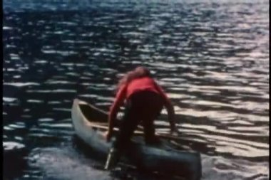 Rear view of woman getting into row boat on lake — Stock Video