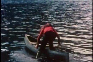 вид сзади женщины, попадая в гребная лодка на озере — Стоковое видео