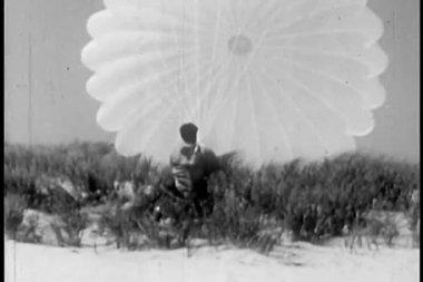 человек борется с открытым парашютом — Стоковое видео