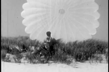 Hombre luchando con un paracaídas abierto — Vídeo de stock