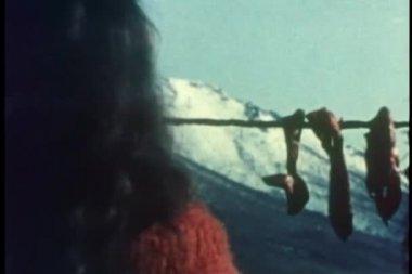 Bakifrån av kvinna hängande remsor av caribou kött att torka — Stockvideo