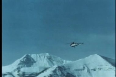 Helicopter flying high over snow capped mountains — Stock Video