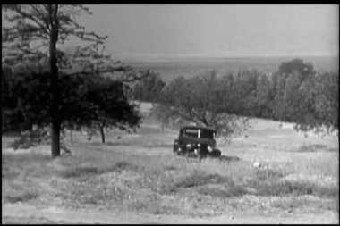 Man in 1940s car driving up to farmhouse — Stock Video