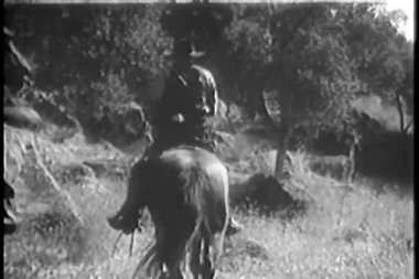 Rear view of group of men on horseback with wounded man — Stock Video