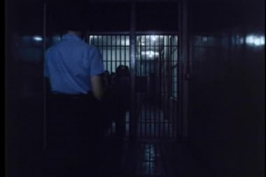 Rear view of prison warden checking on inmates — Stock Video
