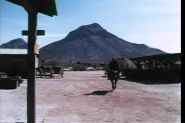 Rear view of man on horseback riding out of town — Stock Video
