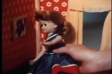 Close-up of girl's hand playing with doll in dollhouse — Stock Video