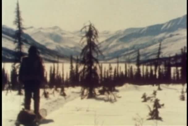 Vue arrière de l'homme en faisant glisser le traîneau dans la neige — Vidéo