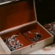 Hand putting earring in jewelry box — Vídeo de stock