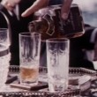 Close-up hand pouring liquor into glass and serving — Vídeo Stock
