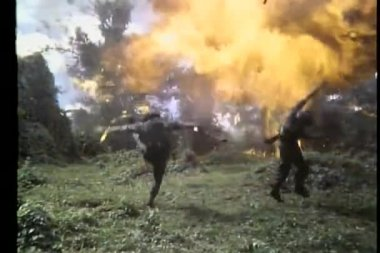 Rear view explosions knocking down troops — Stock Video
