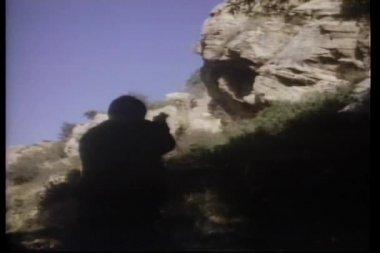 Gun fight on rocky hillside — Stock Video
