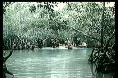 Soldiers and prisoners wading through river — Stock Video