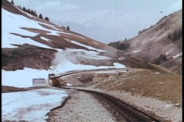 Train driving on railroad track through mountain range — Стоковое видео