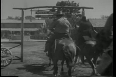 Rear view of cowboys on horseback riding into ranch — Stockvideo