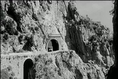 Long shot car driving out of mountain tunnel — Stock Video