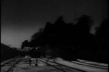 Long shot train pulling into station at night — Stock Video #26663793