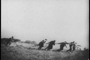 Wide shot of men plowing field — Stock Video
