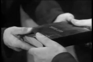 Close-up of hands exchanging a bible — Stock Video