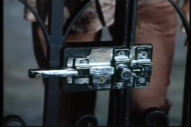 Hands opening gate lock