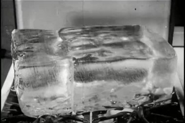 Block of ice melting on stove — Stock Video