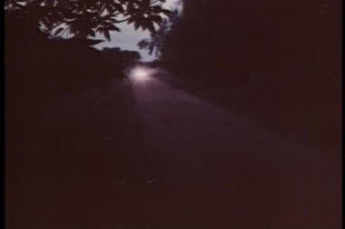 Car driving down country road with headlights on — Stock Video #26664229