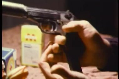 Hands loading gun with silencer — Stock Video #26664461