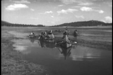 Native Americans paddling down river on canoe