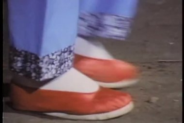 Close-up feet in red Chinese slippers walking across floor — Stock Video