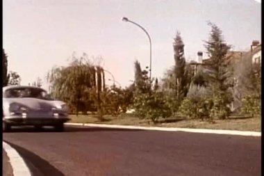 Car speeding past elderly couple waiting to cross the street — Stock Video