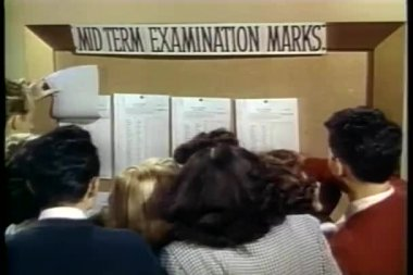 Students checking their mid-term grades posted on board — Stock Video