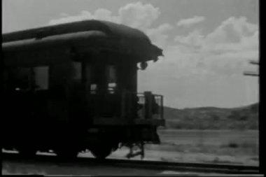 Wide shot cowboy on horseback chasing train — Vídeo Stock