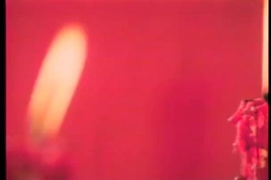 Close-up burning candles in front ot red background — Vídeo de stock