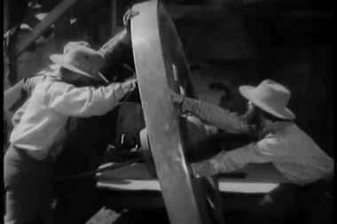 Men moving large wooden wheel — Stock Video #26665009
