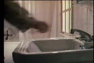 关闭滴水的龙头在浴室中的人 — 图库视频影像
