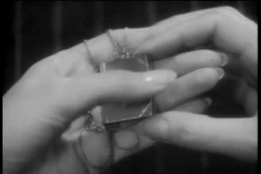 Close-up of hands opening locket with note inside — Stock Video
